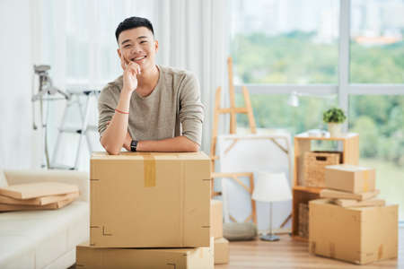Happy handsome ethnic man in casual clothes standing leaning on pile of large cardboard boxes for moving and looking at camera smiling with finger at cheek on blurred background of packed cartons and  스톡 콘텐츠