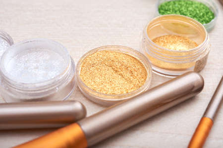 Close-up shot of composed small cans with bright glitters and cosmetic brushes on table