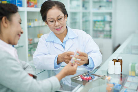 Smiling pharmacist explaining suggested use of medicine to customer Stock fotó - 105229507