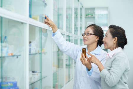 Femme senior souriante demandant au pharmacien de montrer son médicament Banque d'images