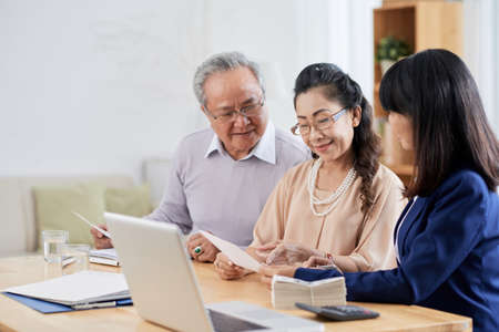 Vietnamese senior couple meeting with financial adviser