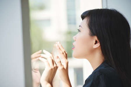 Inspired ambitious beautiful Asain woman looking through office window