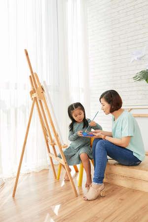 Vista laterale della donna asiatica dell'insegnante e della ragazza dell'allievo che si siede e che disegna al cavalletto nella classe di arte