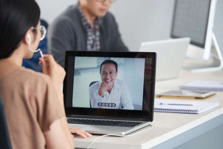 Crop back view of woman in glasses and earphones talking with smiling man via video chat on laptop sitting at office desk on blurred background