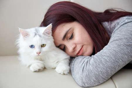 Woman sleeping on Fluffy cat like a pillow