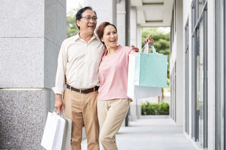 Cheerful senior woman showing something in shop window to her husband Stock Photo