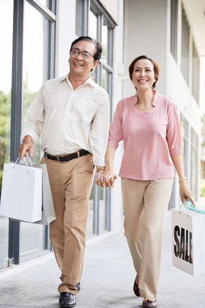 Happy aged husband and wife holding hands when shopping on weekend Foto de archivo