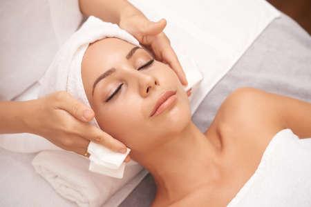Piękna młoda kobieta z nieskazitelną skórą, ciesząc się profesjonalną twarz w gabinecie kosmetycznym