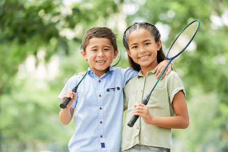 Asian boy and girl with badminton racquets smiling and looking at camera while standing on blurred background of park