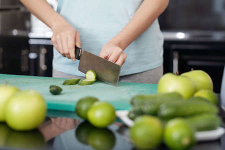 Unrecognizable female slicing fresh cucumber while cooking in modern kitchen Banco de Imagens