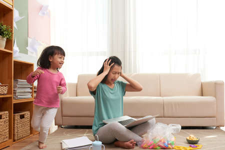 Stressful Asian woman with laptop sitting on floor and pressing head with noisy girl running around Foto de archivo