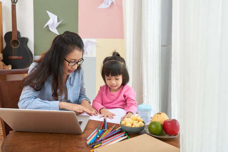 Adult woman with laptop working at home and with little girl drawing together at table