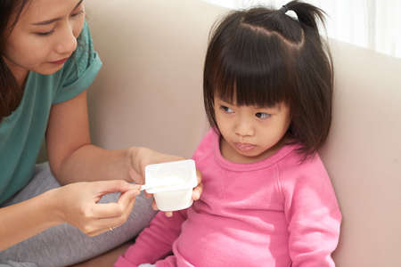 Asian woman feeding little girl sitting on sofa and giving spoon with yogurt Banco de Imagens - 106551484