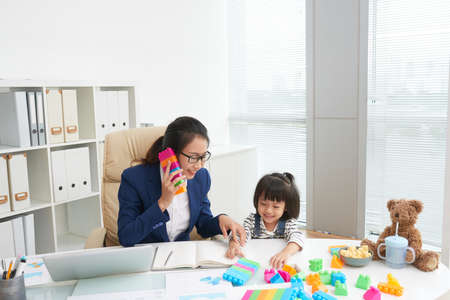 Cheerful Asian businesswoman and charming daughter playing with colorful blocks at table in work office Stock fotó