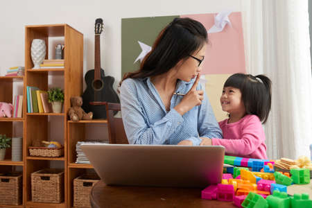 Asian woman with laptop working at home and asking playful little daughter to be quiet