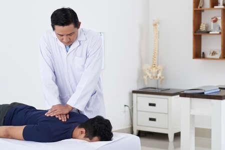 Chiropractor adjusting spine