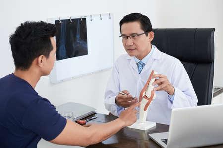 Doctor explicando la estructura de la articulación al paciente Foto de archivo