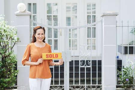 Porträt der hübschen reifen asiatischen Frau verkaufte ihr Haus