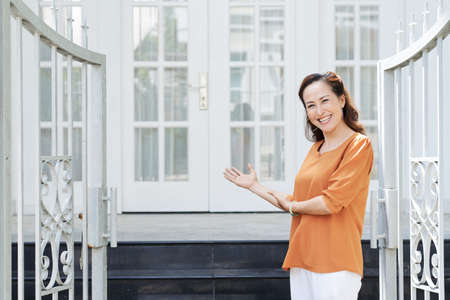 Happy mature Asian woman inviting you to enter her house Stock Photo
