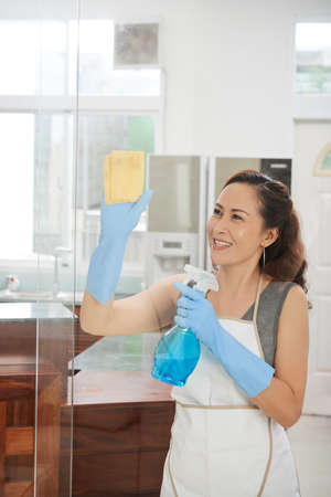 Cheerful mature Asian woman wiping glass door or window in kitchen