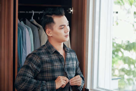 Asian man buttoning checkered shirt while getting dressed in room with wardrobe at home looking away Stock Photo
