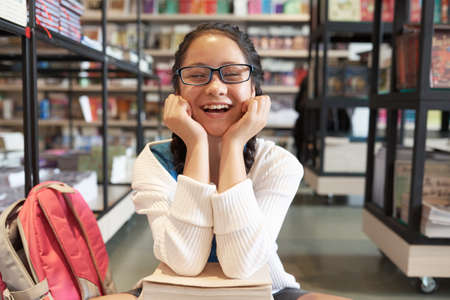 Girl in glasses sitting with head on hands smiling with closed eyes on blurred bookshelves background