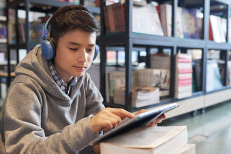 Young student boy with tablet and headphones studying in library