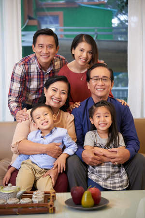 Cheerful Asian parents, grandparents and children smiling at camera Banco de Imagens