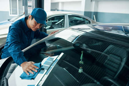 Vietnamese mechaninc wiping windshield with soft cloth