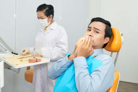 Adult Asian man covering mouth in fear while sitting in dental char in office with doctor and looking at camera