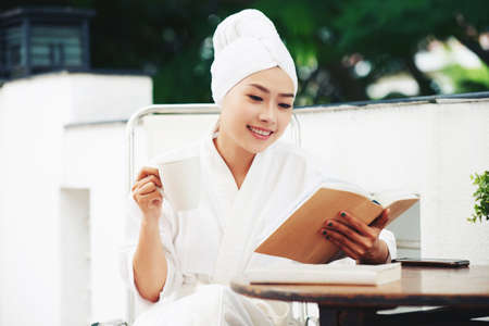Young Asian woman in towel and white bathrobe reading book on terrace having cup of coffee