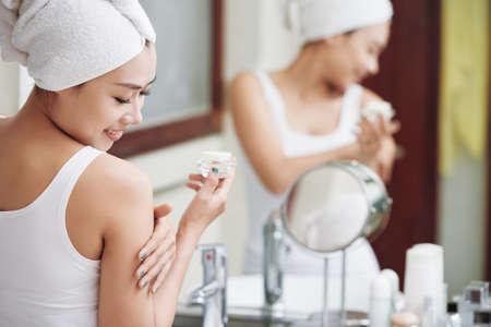Jolie femme asiatique dans la salle de bain adoucissant la peau avec une lotion souriant joyeusement