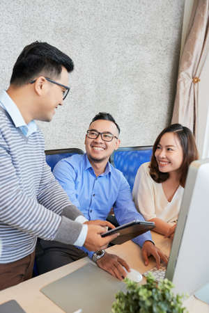 Modern Asian men and woman gathering at table in office using tablet and communicating cheerfully
