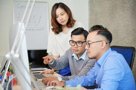 Groep Aziatische mannen en vrouw aan tafel in moderne kantoor kijken naar computer en praten over project