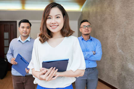 Modern young Asian woman with male coworkers on background standing with tablet in office smiling at camera Stock Photo