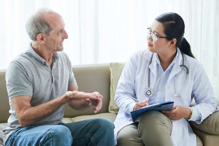 Elderly man sharing complaints with adult ethnic doctor during home visit sitting on sofa Stock Photo