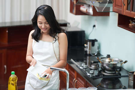 Charming Asian woman in white apron washing dishes with sponge standing in modern kitchen Banque d'images