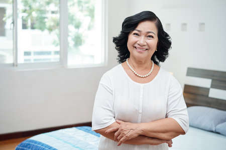 Waist-up portrait of attractive retired Asian woman with pearl necklace standing in bedroom with crossed hands and smiling at camera Stockfoto