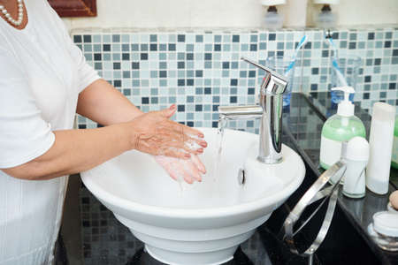 Unrecognizable mature woman washing hands with soap thoroughly while standing by sink in modern bathroom