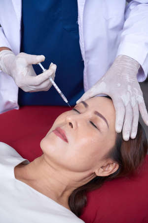 Beautiful woman receiving treatment with botox or hyaluronic collagen injection at clinic