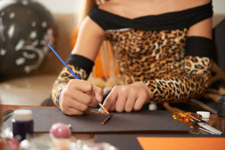 Unrecognizable girl wearing smart leopard dress using brush while making handicraft for Halloween party