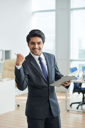 Businessman standing with notepad at office and he is happy because he did all his work