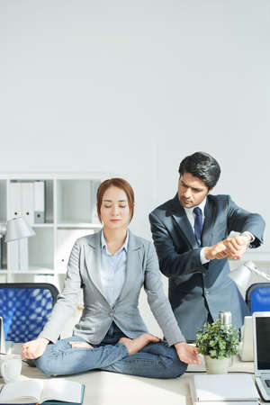 Dissatisfied businessman hurrying his colleague while she meditates on the table