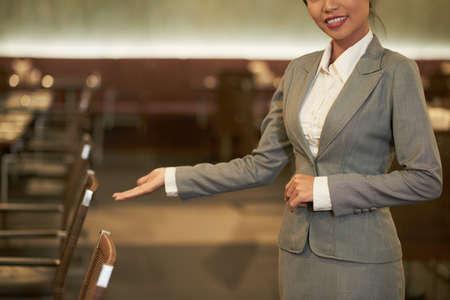 Ernten Sie elegante Frau im Anzug, die eine einladende Geste macht, die zum Besuch des Restaurants im Hotel einlädt