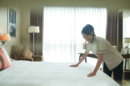 Young Asian woman in uniform making fresh bed and flattening white blanket in hotel room Stock Photo
