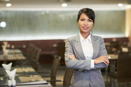 Smiling elegant Asian woman in suit working as hostess in hotel restaurant looking at camera Stok Fotoğraf