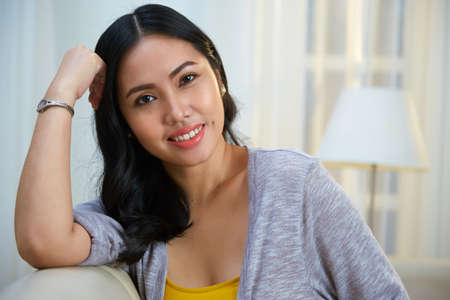 Attractive Filipino lady smiling and looking at camera while leaning on soft back of comfortable couch in cozy living room Stock Photo