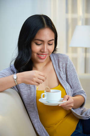 Charming Filipino female smiling and brewing aromatic tea while sitting on comfortable couch in cozy living room