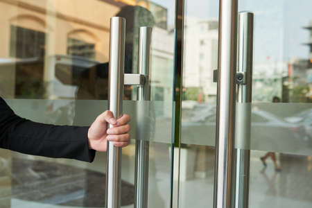 Faceless shot of hotel worker in black suit opening glass doorway to guest