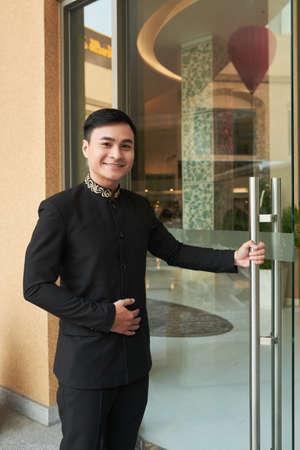 Hombre asiático en elegante traje negro abriendo la puerta de cristal del hotel saludando a los huéspedes